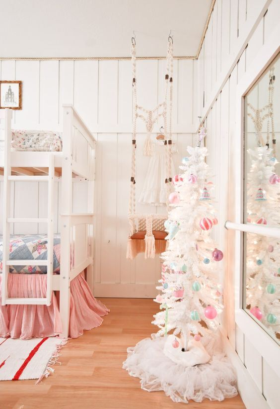 a white Christmas tree with pastel ornaments and lights is all you need to create a holiday atmosphere in the space