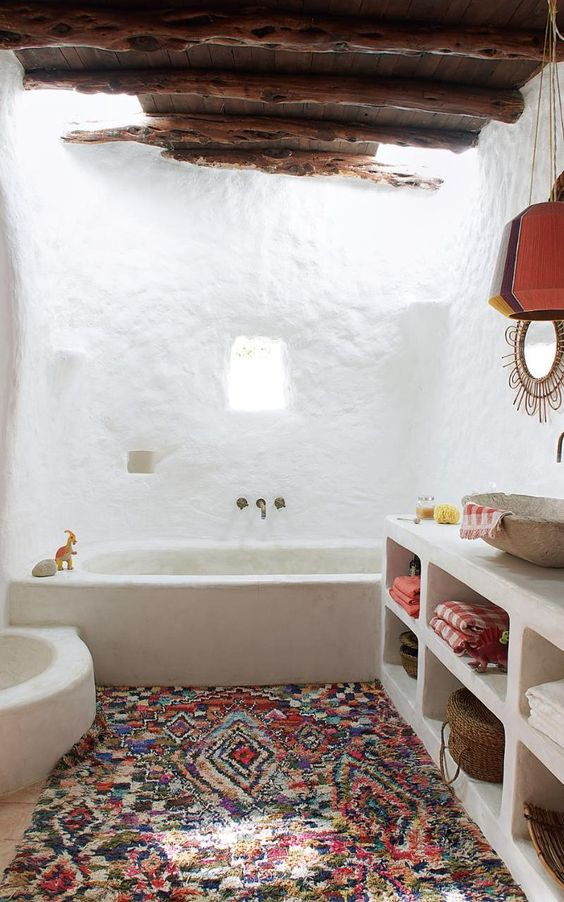 a boho bathroom with white walls, a stained ceiling with beams, a boho rug and a concrete vanity
