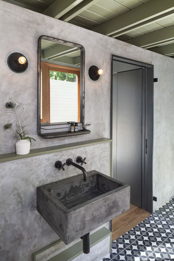 a catchy bathroom with a patterned tile floor, concrete walls and a floating sink, a mirror and bulbs plus a shelf