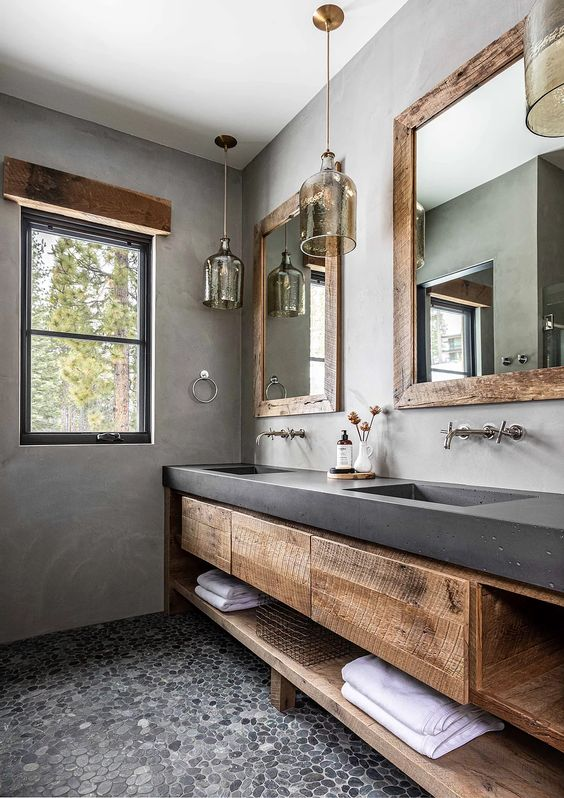 a catchy bathroom with concrete walls and a vanity, wooden storage units, pendant lamps and mirrors in rough wooden frames