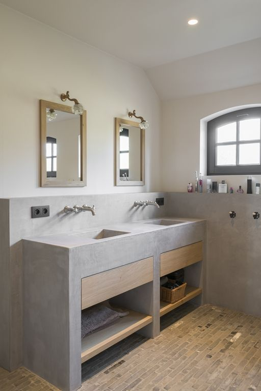 a catchy contemporary bathroom with a tiled floor, a built-in concrete vanity with sinks, mirrors in wooden frames and wooden drawers