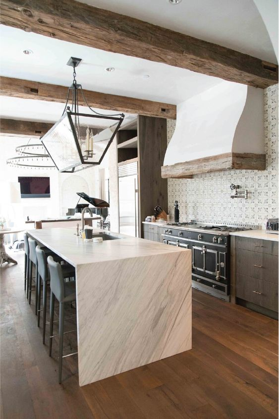 a catchy kitchen with dark cabinetry, a white stone kitchen island, rough wooden beams and a refined chandelier