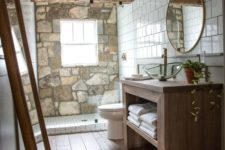 a chalet bathroom with a stone accent wall, a wooden beam, a wooden vanity and a round mirror looks very cozy