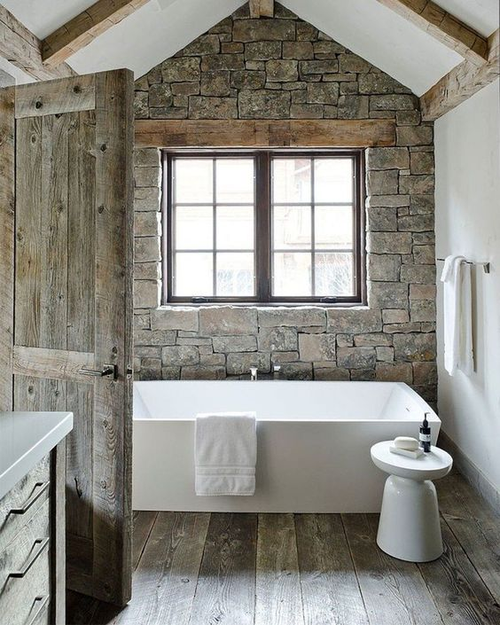 a chalet bathroom with a stone accent wall, wooden beams on the walls and ceiling, a bathtub and a side table plus a window