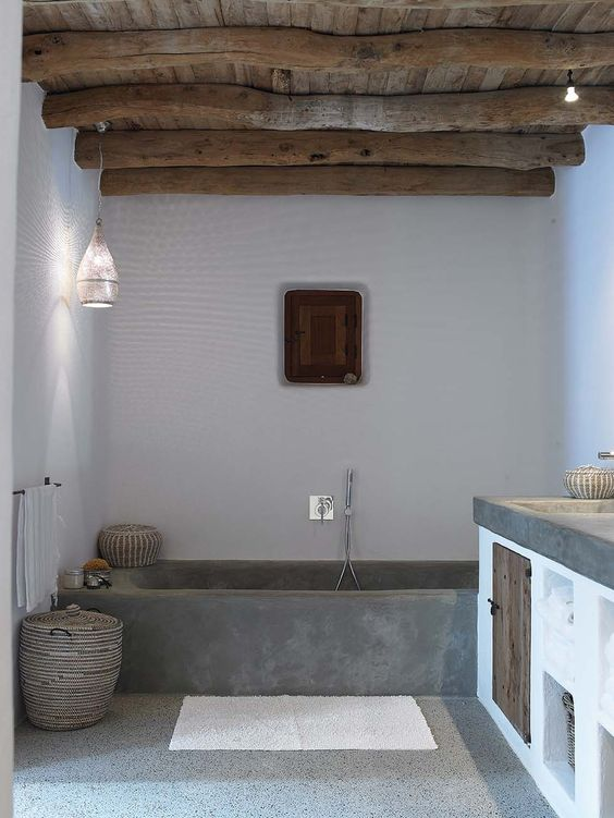 a chic bathroom with white walls, a concrete bathtub, a wooden ceiling and beams and a concrete vanity