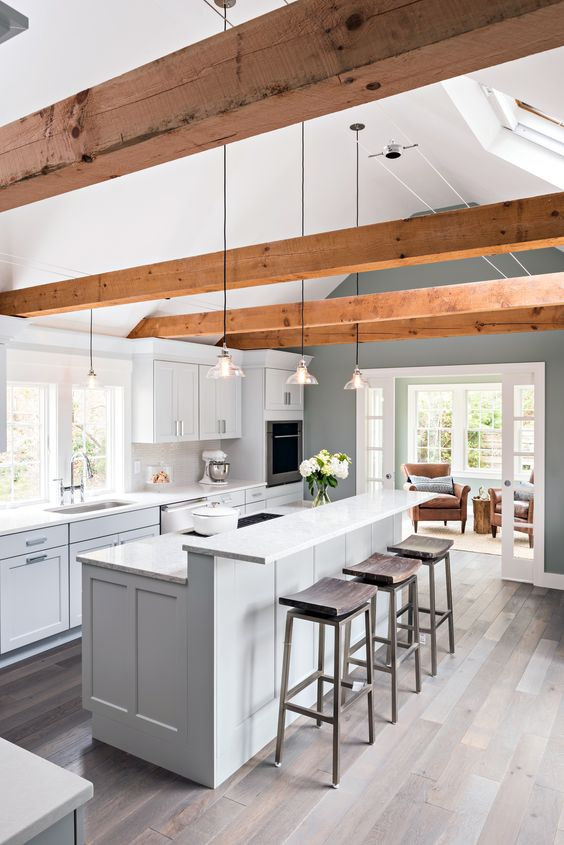 a chic dove grey contemporary kitchen with a two-level kitchen island, rich-tone woodne beams, pendant lamp and dark wooden stools