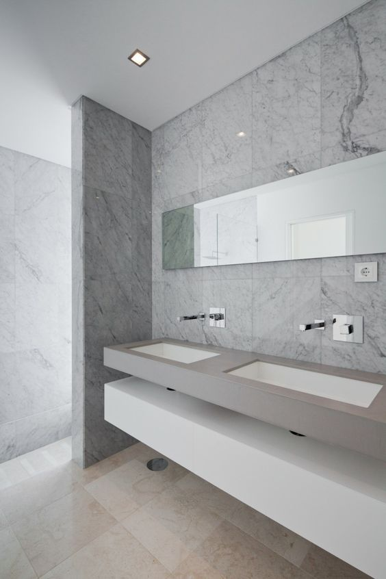 a chic minimalist bathroom with marble patterned tiles, a floating concrete vanity with sinks and a white slab shelf plus a long mirror