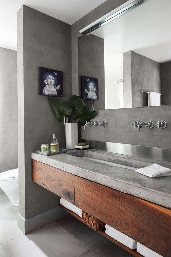 a concrete bathroom with a concrete vanity and wooden storage units, a large mirror and a window to enjoy natural light