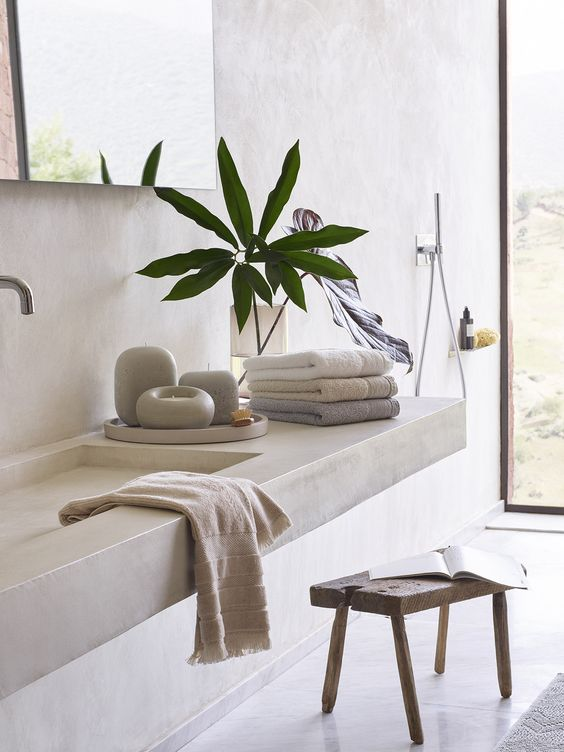 a concrete bathroom with a floating concrete vanity and a sink, a wooden stool, large mirrors and pretty towels