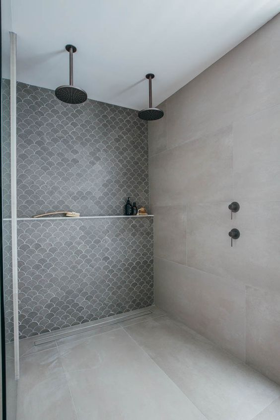 a concrete bathroom with an accent fish scale tile wall and dark brass fixtures is a pretty and cool space