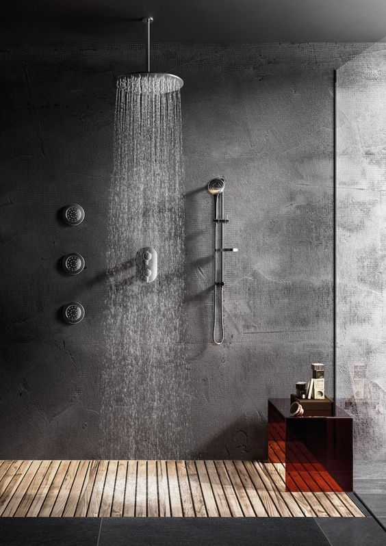 a concrete shower space with a wooden floor, a glass wall and a dark glass mini bench is a cozy and cool space