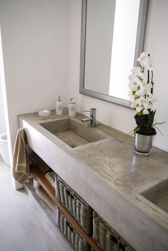 a concrete vanity with a double built-in sink and wooden shelves, mirrors in simple frames and basket drawers for storage