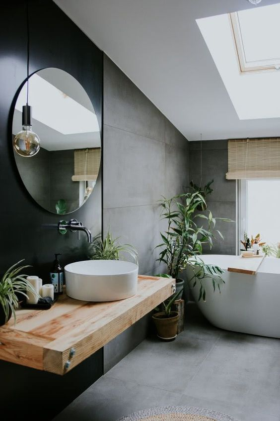 a contemporary attic bathroom with concrete walls and a floor, a black accent wall with a floating vanity and a round mirror