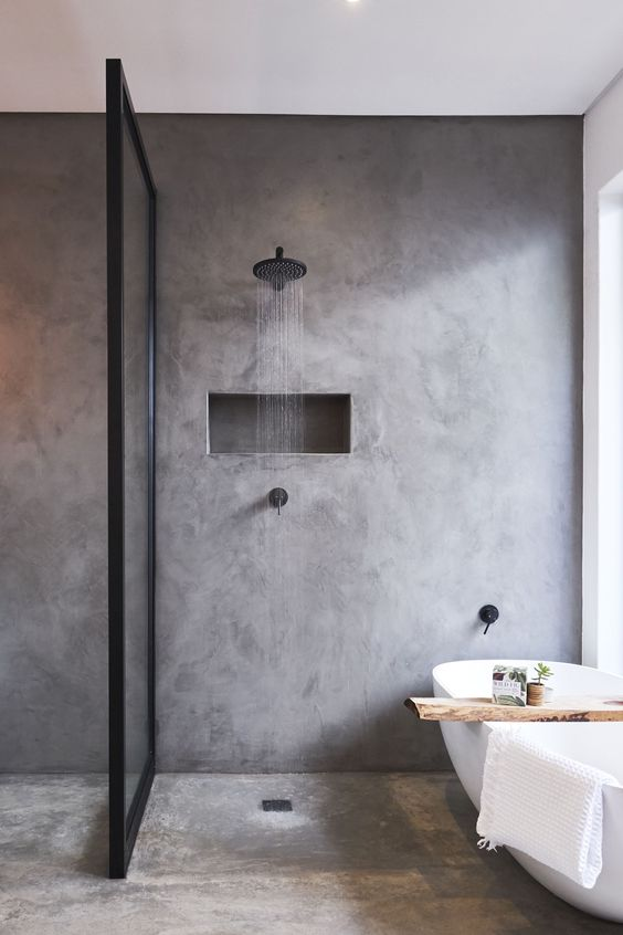 a contemporary bathroom of concrete, with a framed glass partition, an oval tub and black fixtures for a modern feel