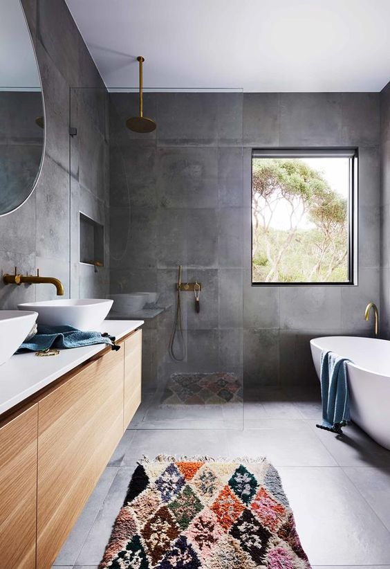 a contemporary bathroom with a concrete floor and walls, a floating vanity and brass fixtures plus an oval tub