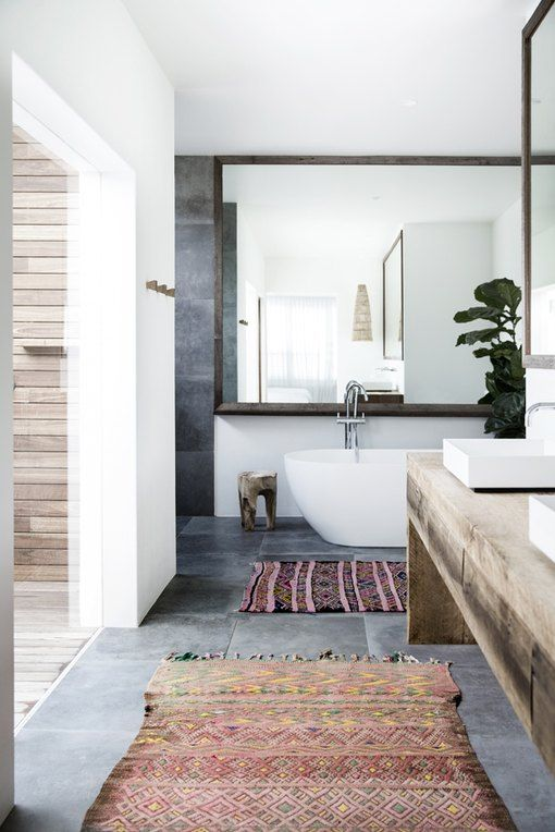 a contemporary bathroom with a concrete floor and walls, an oval tub, a double wooden vanity, square sinks and a large mirror wall