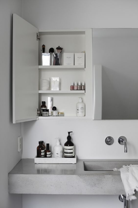 a contemporary bathroom with a mirror, built-in cabinets and a concrete floating vanity plus simple fixtures looks fresh