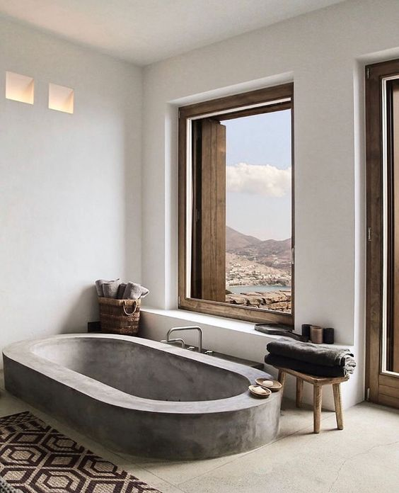 a contemporary bathroom with windows fo a view, a concrete floor and a built-in concrete bathtub, a printed rug and wooden sotols
