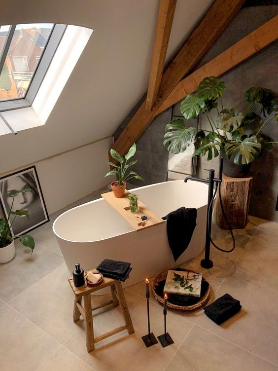 a contemporary bathroom with wooden beams, a grey tile wall, a bathtub, black textiles and candles