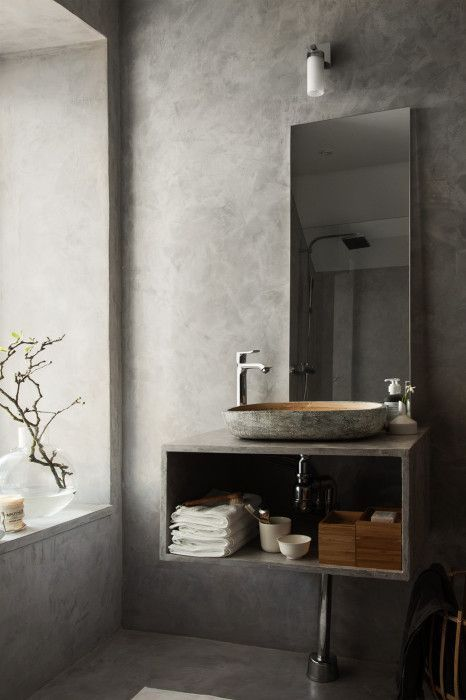 a contemporary concrete bathroom with a window, an open storage vanity, a sink carved of stone and a mirror