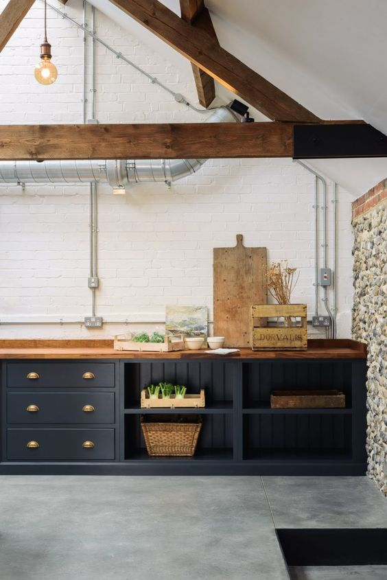 a contemporary kitchen with navy cabinets, a white brick wall, wooden beams and exposed pipes for an eye-catchy touch