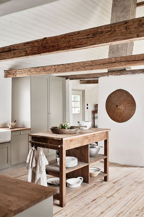 a contemporary neutral kitchen in white and dove grey, a wooden kitchen island, wooden beams for a welcoming feel