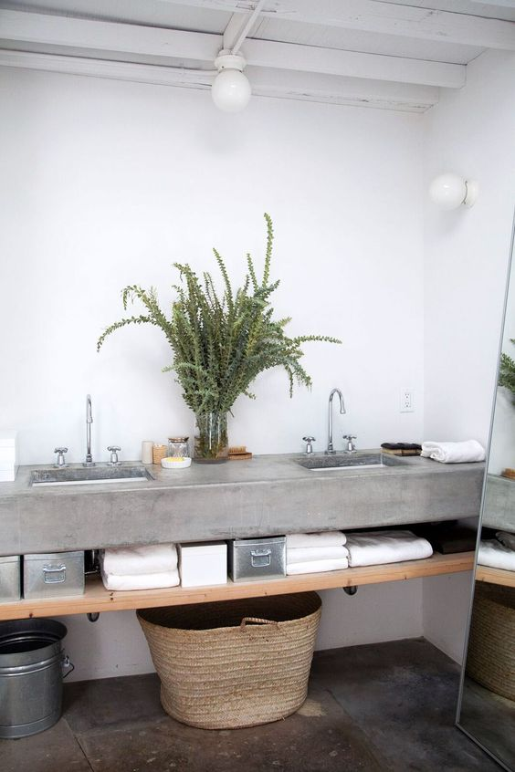 a contemporary rustic bathroom with a concrete floating vanity and a concrete floor, a wooden shelf, greenery and a floor mirror
