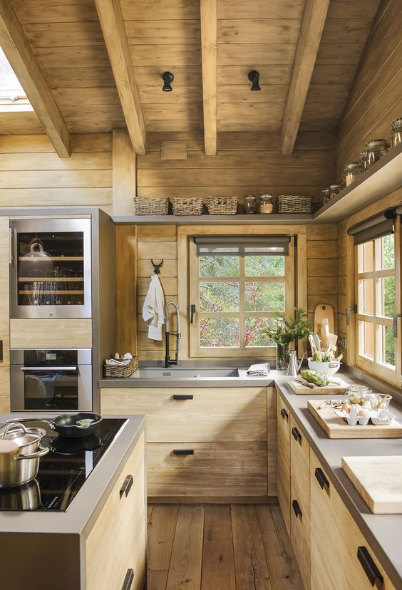 a contemporary wooden chalet kitchen with concrete countertops, skylights, wooden beams on the ceiling is chic and light-filled