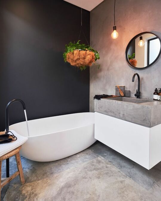 a contrasting bathroom with a black accent wall, floors, walls and a sink of concrete, black fixtures and a round mirror