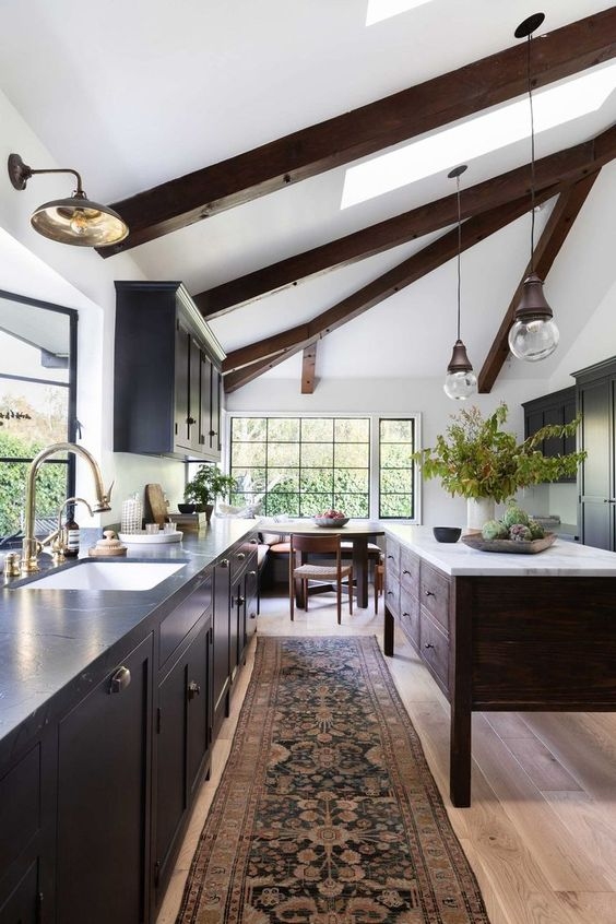 a contrasting kitchen with dark cabinets and a stained kitchen island, dark wooden beams, pendant lamps and lights