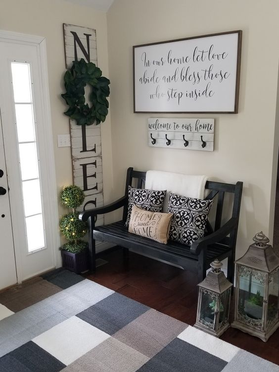 a cozy famrhouse entryway with a blakc vintage bench, candle lanterns, a sign and a colored rug