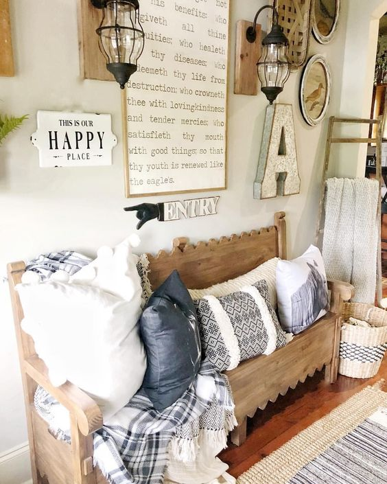 a cozy farmhouse entryway with a carved wooden bench, a gallery wall with signs and lamps, printed pillows and a blanket