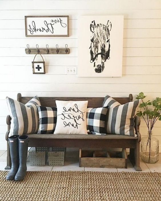 a cozy farmhouse entryway with a dark stained bench, printed pillows, some artworks and a large jute rug