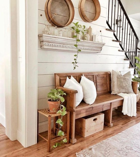 a cozy modern farmhouse entryway with a wooden bench, a stool, some wooden bowls and a whitewashed rack with bottles