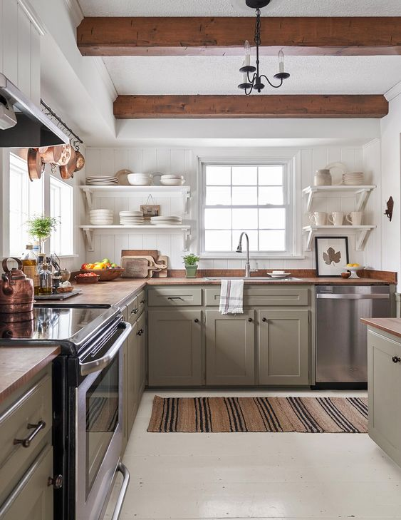 a cozy modern farmhouse kitchen with green cabinetry, wooden countertops and wooden beams that match and warm up the space