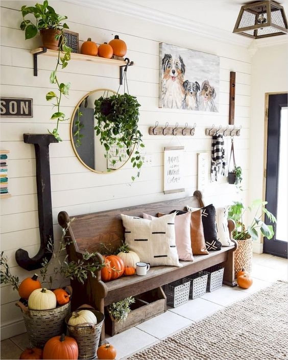 a fall farmhouse entryway with a wooden bench, some racks and shelves, a gallery wall and lots of pumpkins