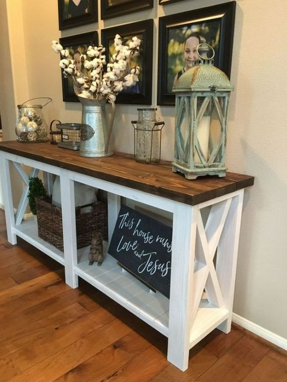 a farmhouse console with a rich stained tabletop, a chalkboard sign, a cotton branch arrangement and a gallery wall