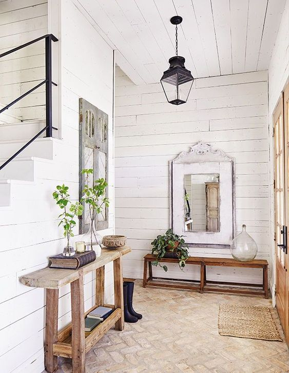 a farmhouse entryway with a console and a bench, a lamp, a jute rug, some greenery in vases and mirrors