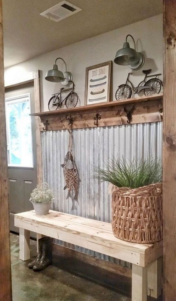 a farmhouse entryway with a corrugated steel wall, a rack with hooks, some metal lamps and a basket with greenery