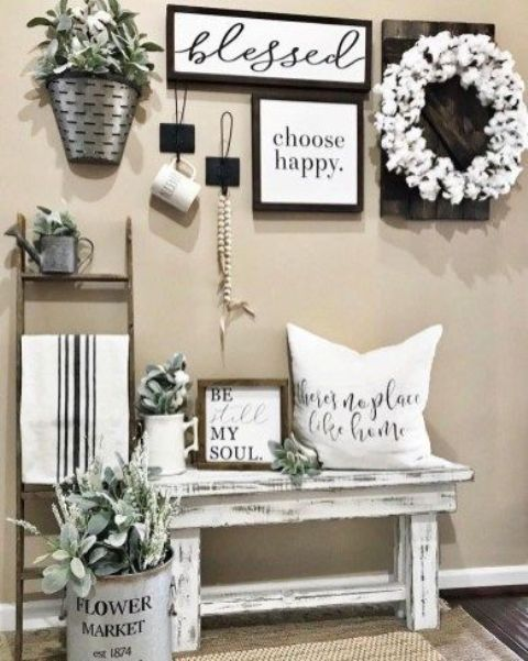 a farmhouse entryway with a monochromatic gallery wall, a whitewashed bench and some greenery arrangements