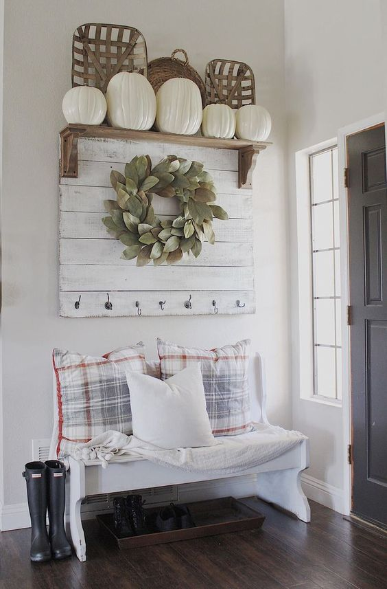 a farmhouse entryway with a white bench, checked pillows, a white rack, a wreath and a rack with white pumpkins for fall
