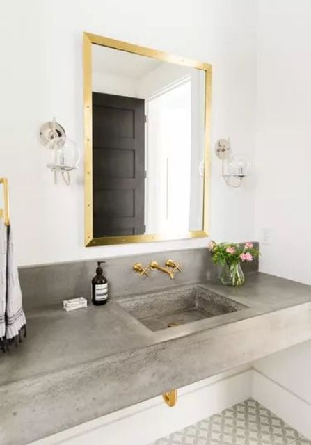 a floating concrete vanity with a sink, bold gold fixtures to glam up this nook for a cool and contemporary space
