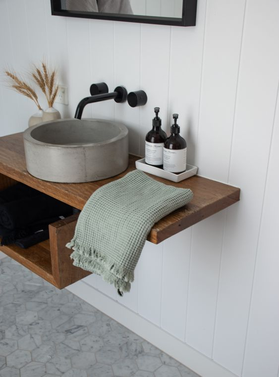 a floating wooden vanity with a round concrete sink and black fixtures is a bold and cool solution for a modern bathroom
