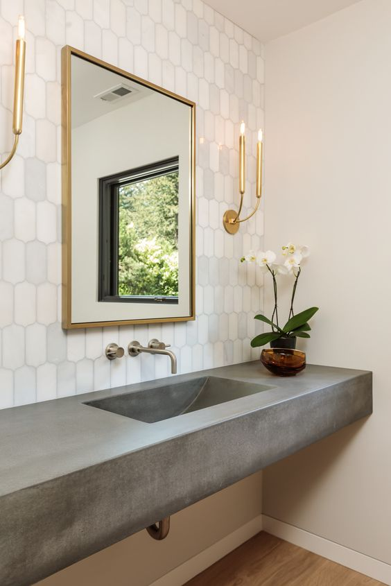 a glam bathroom with a white tile wall, a concrete vanity with a built-in sink, a mirror in a gilded frame and gilded sconces