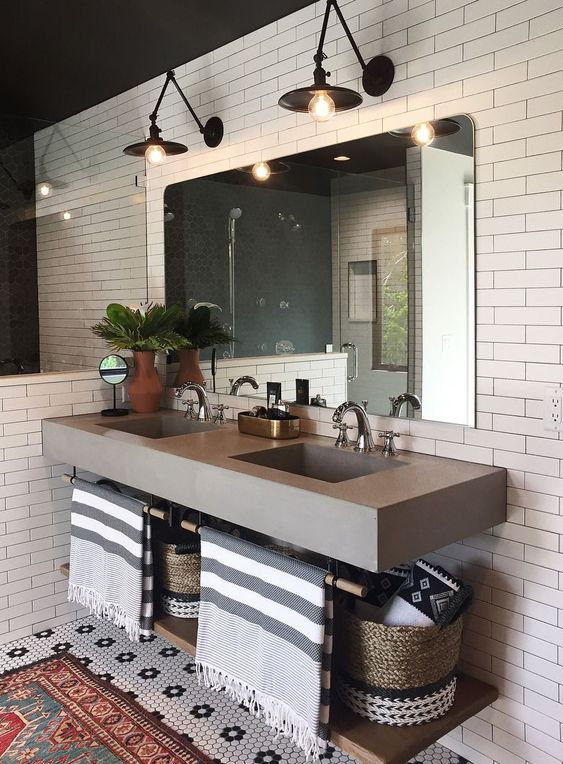 a mid-century modern bathroom clad with white tiles, a concrete floating vanity, black sconces and a large mirror plus baskets for storage