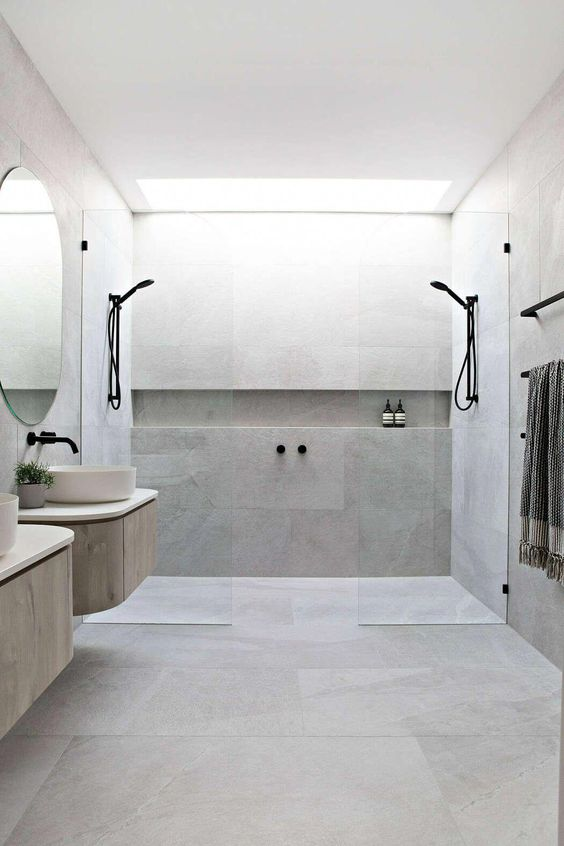 a minimalist bathroom clad with concrete, two floating vanities, round sinks, black fixtures and glass partitions