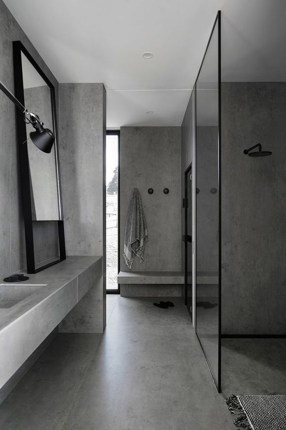 a minimalist bathroom fully made of concrete, with a concrete vanity, glass partitions, a framed mirror and a large window