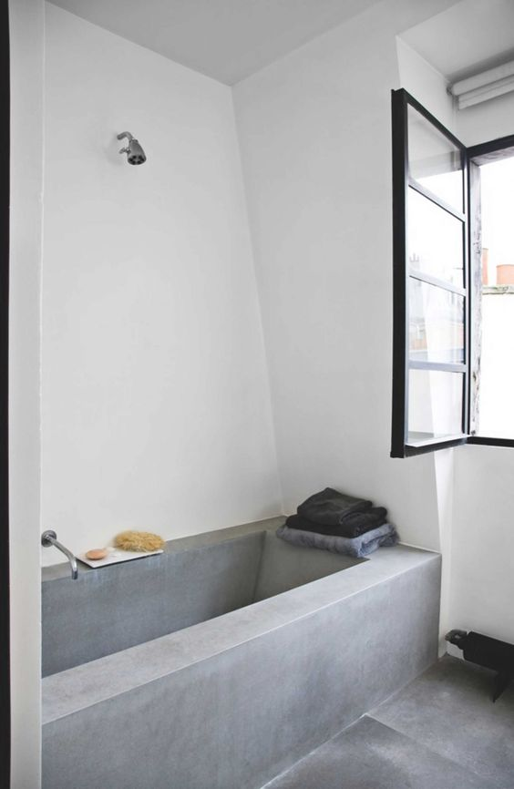 a minimalist bathroom with a concrete tub and a floor, a window for natural light and simple fixtures is cool