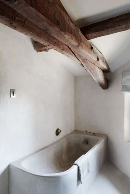 a minimalist bathroom with white walls, a concrete tub and rich stained wooden beams for a softer and warmer look