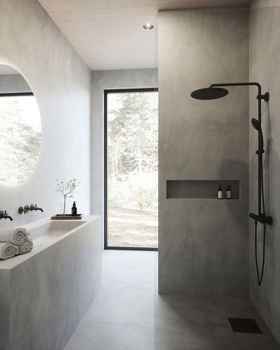a minimalist concrete bathroom with a built-in vanity and a sink, a shower space, a glazed wall and black fixtures